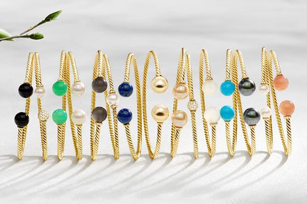 A horizontal stack of Solari bracelets in 18K yellow gold with a chromatic array of gemstones shot against a white stone backdrop with budding branches on one side and long shadows.