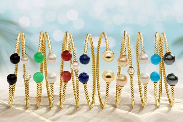 A color photo shows a horizontal row of David Yurman Solari bracelets standing upright and casting long shadows on a light sandy beach. In the out-of-focus background are palm trees flanking either side of a blue sea with sunlight glittering on its surface. The jewelry is crafted from 18K yellow gold with colored gemstone, cultured pearl or pavé white diamond orbs.