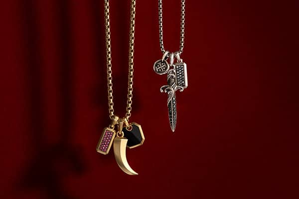 Men's Streamline and Roman amulets in 18K yellow gold with or without rubies or black onyx, strung on a box-chain necklace in 18K yellow gold, hang next to Shipwreck, Waves and Streamline charms in sterling silver with or without black diamonds, strung on a box-chain necklace in sterling silver, all against a dark red background.