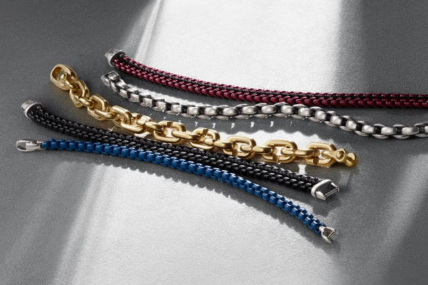 Men's Chain bracelets in blue stainless steel, black stainless steel and black nylon, 18K yellow gold, sterling silver and a burgundy stainless steel with black nylon, arranged in a diagonal row atop a white textured surface.