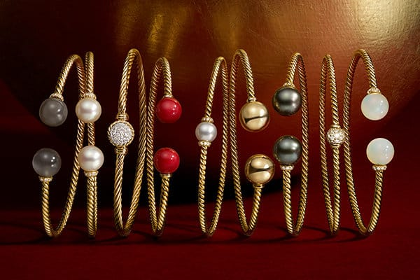 A horizontal stack of Solari and Cable bracelets in 18K yellow gold with a chromatic array of gemstones shot against a red backdrop with golden light.