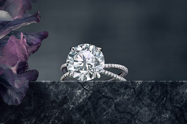 A color photograph shows a DY Crossover engagement ring atop a dark, marbled stone surface with dark solid background and with a flower petals to the right.