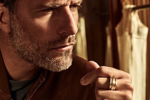 A color photo shows a close-up of man wearing a dark brown leather jacket, a crewneck t-shirt, and a David Yurman men's Deco signet ring crafted from 18K yellow gold. He is standing in front of brown wood walls and open beige window curtains, and is staring, with a furrowed brow, to the right of the camera. The left part of his faced turned towards the camera is shrouded in shadow,