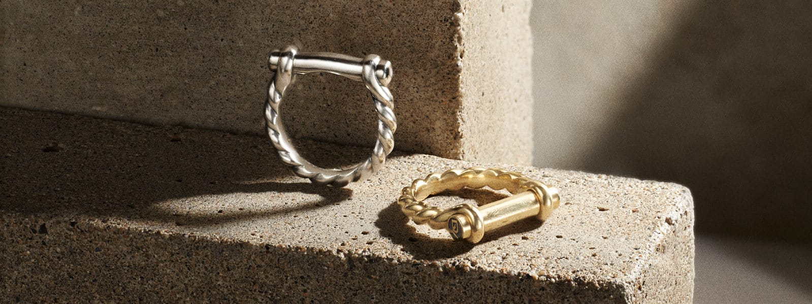 Maritime® shackle rings in sterling silver and 18K yellow gold in the light on a warm-hued stone.