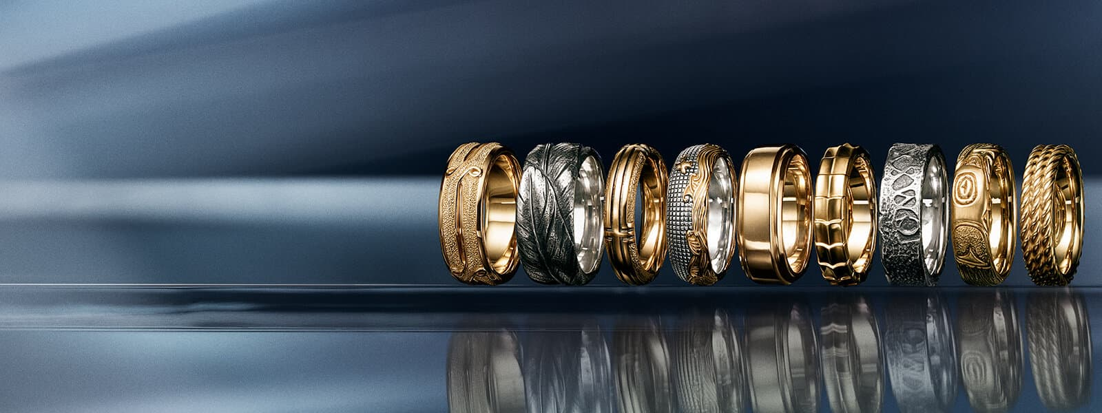 A color photograph shows a horizontal row of nine David Yurman men's band rings from the Armory®, Southwest, Waves, Deco, Shipwreck, Northwest and Maritime® collections atop a reflective surface with angular, multi-colored reflections of light and jewelry and in front of a dark ombré background. One of the Southwest bands and the Shipwreck band are crafted from sterling silver. The Waves band is crafted from sterling silver with 18K yellow gold. All of the other bands are crafted from 18K yellow gold.