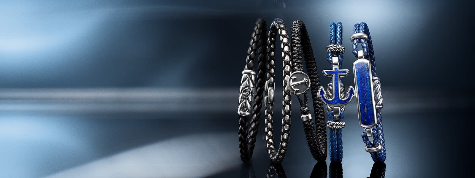A color photograph shows a horizontal stack of five David Yurman men's bracelets from the Chevron, Chain and Maritime® collections atop and in front of reflective surfaces with angular, multi-colored reflections of light. The Chevron bracelet is crafted from woven black rubber with sterling silver. The Chain and one of the Maritime® bracelets are crafted from woven black nylon with sterling silver. The rest of the Maritime® bracelets are crafted from woven blue leather with sterling silver and inlaid lapis lazuli in the shape of an anchor or the bar in an ID bracelet.