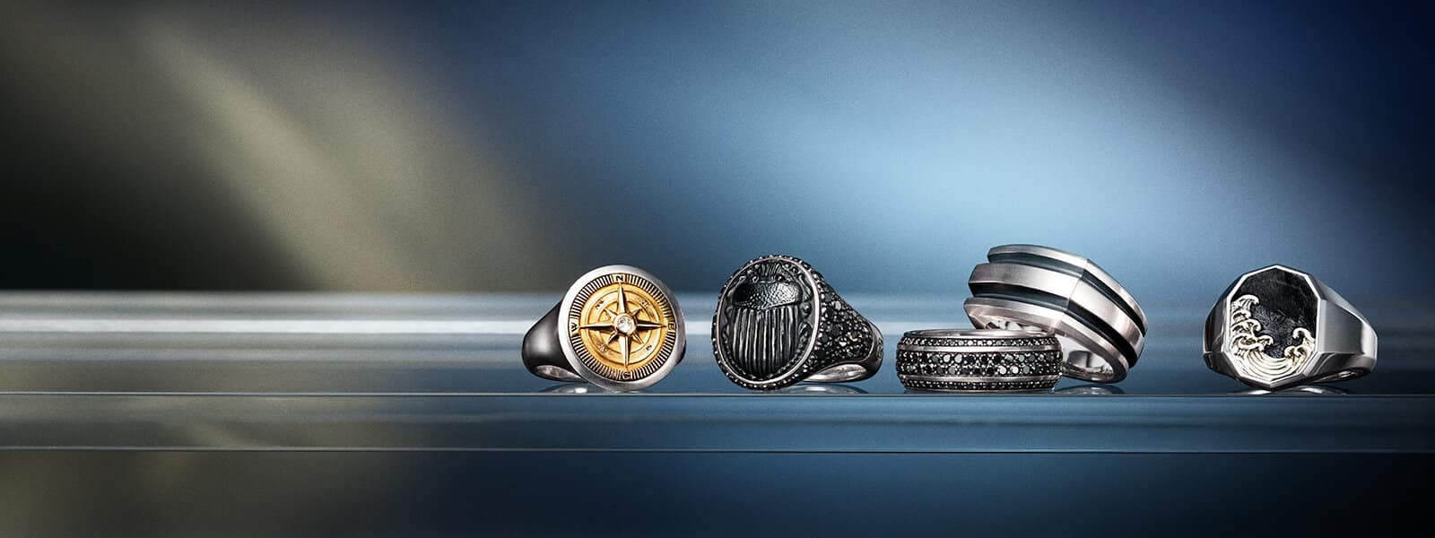 A color photograph shows a horizontal row of David Yurman men's rings from the Maritime®, Petrvs®, Beveled Deco and Waves collections atop and in front of reflective surfaces with angular, multi-colored reflections of light. The Maritime® compass ring is crafted from sterling silver with 18K yellow gold and a white diamond center stone. The Petrvs® scarab ring is crafted from sterling silver with black onyx and pavé black diamonds. The Beveled band ring is crafted from 18K white gold with black diamonds. The Deco cigar band ring is crafted from sterling silver. The Waves signet ring is crafted from sterling silver with forged carbon.