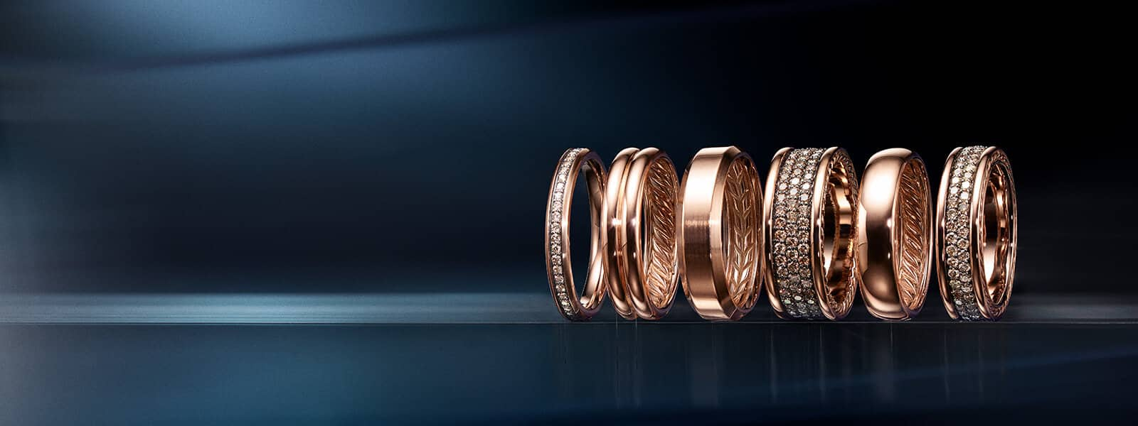 A color photograph shows six David Yurman men's band rings in various widths from the Streamline®, DY Classic and Beveled collections atop a reflective surface with angular, multi-colored reflections of light and jewelry, and in front of a multi-colored background. The rings are shot to appear as if they're moving. The DY Classic and Beveled bands are crafted from 18K rose gold. All of the Streamline® bands are crafted from 18K rose gold with pavé cognac diamonds.