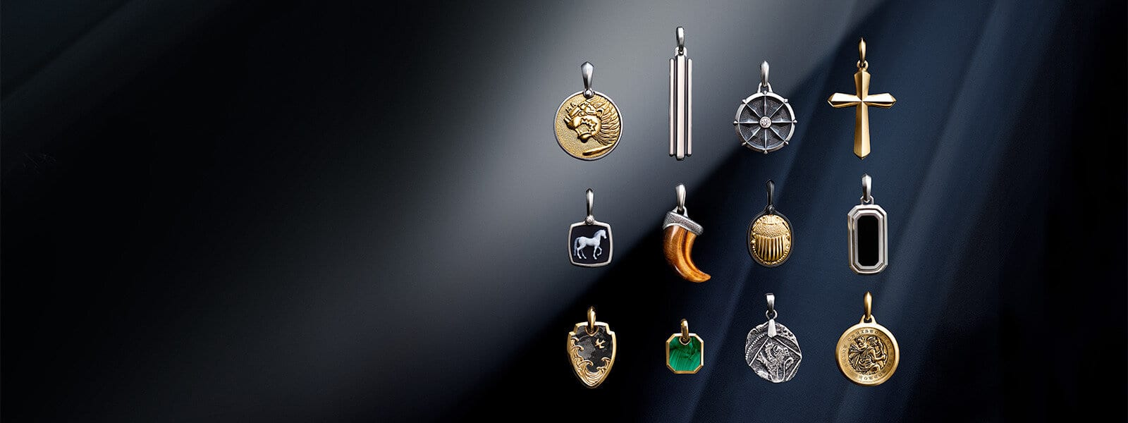 A color photograph shows a three-by-four grid of David Yurman men's amulets from the Petrvs®, Deco, Maritime®, Amulets, Roman, Waves and Shipwreck collections atop a reflective surface with angular, multi-colored reflections of light. The Petrvs® lion amulet is crafted from sterling silver with 18K yellow gold. One of the Deco amulets is crafted from sterling silver, while the other is crafted from sterling silver with black onyx. The Maritime® amulet is crafted from sterling silver with a white diamond center stone. The Petrvs® horse amulet is crafted from sterling silver with banded agate. The Amulets claw is crafted from tiger's eye with sterling silver. The Petrvs® scarab amulet is crafted from black titanium with 18K yellow gold. The Waves shield amulet is crafted from 18K yellow gold with forged carbon. One of the Roman amulets is crafted from 18K yellow gold with malachite, while the other is a cross crafted from 18K yellow gold. The Shipwreck coin amulet is crafted from sterling silver. The St. Christopher amulet is crafted from 18K yellow gold.