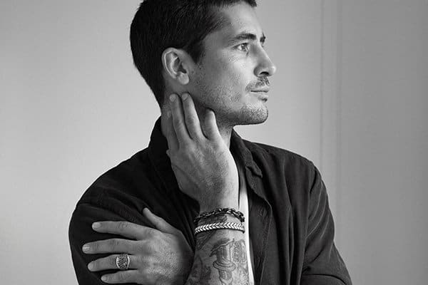 A black-and-white photo shows a headshot of a male model wearing David Yurman jewelry.