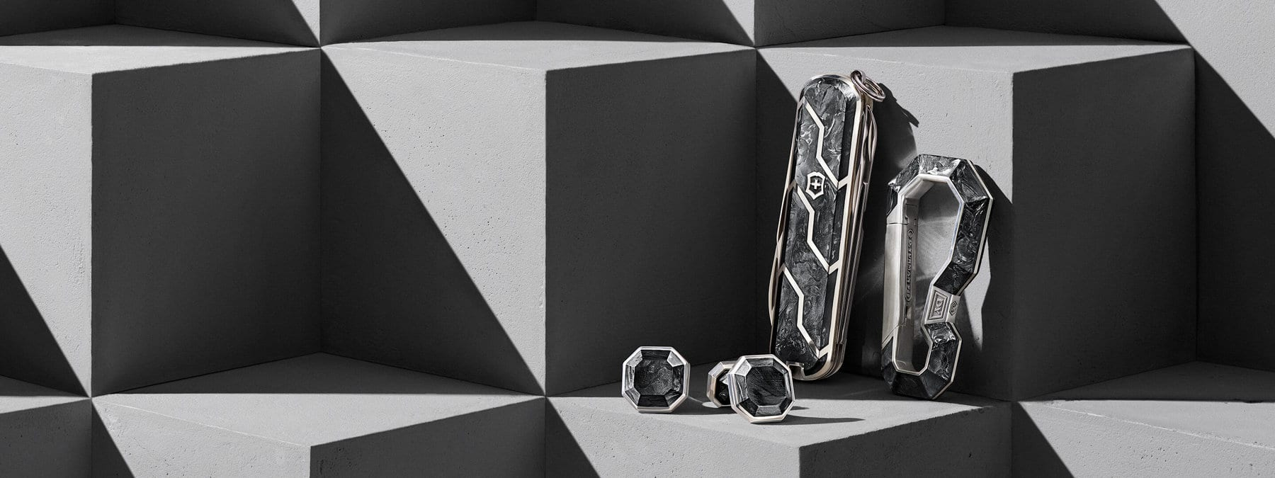 A color photograph shows three accessories from the Forged Carbon Collection atop gray concrete blocks with graphic shadows. From left to right are a pair of cufflinks, a Swiss army knife and a carabineer keychain. Each is crafted from sterling silver and forged carbon.