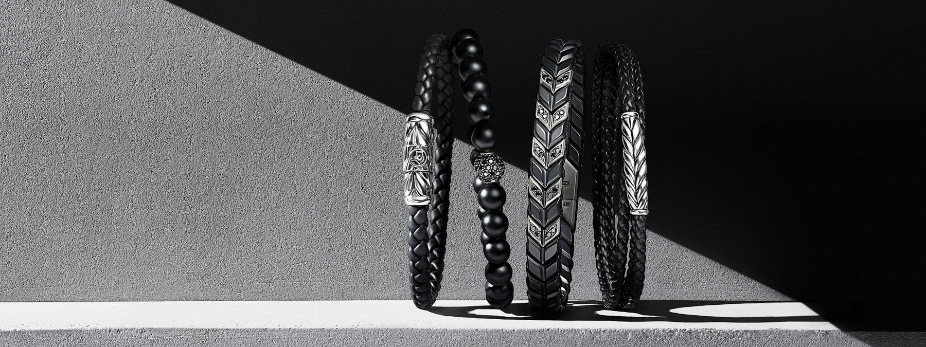 A color photograph shows a row of four David Yurman men's bracelets from the Chevron and Spiritual Beads collections standing upright on grey concrete with a graphic shadow in the background. Two of the bracelets are crafted from sterling silver with woven black rubber or woven smooth black leather. One bracelet is crafted from black onyx beads with sterling silver and pavé black diamonds. One bracelet is crafted from black titanium and black diamonds.