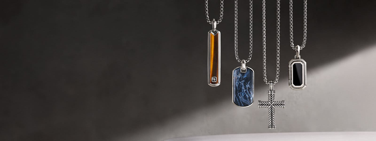 David Yurman Men's Exotic Stone, Chevron cross and Deco pendants, in sterling silver with or without tiger's eye, pietersite or black onyx, each hanging on a sterling silver box chain in front of a stone wall with a ray of light.