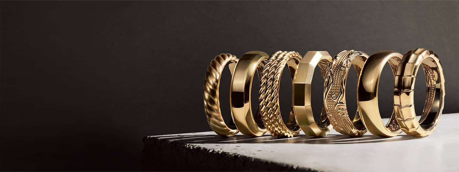 A horizontal stack of David Yurman men's The Cable Collection®, Beveled, Maritime®, Faceted, Waves, DY Classic and Armory® bands, all in 18K yellow gold, casting long shadows on a white stone surface.