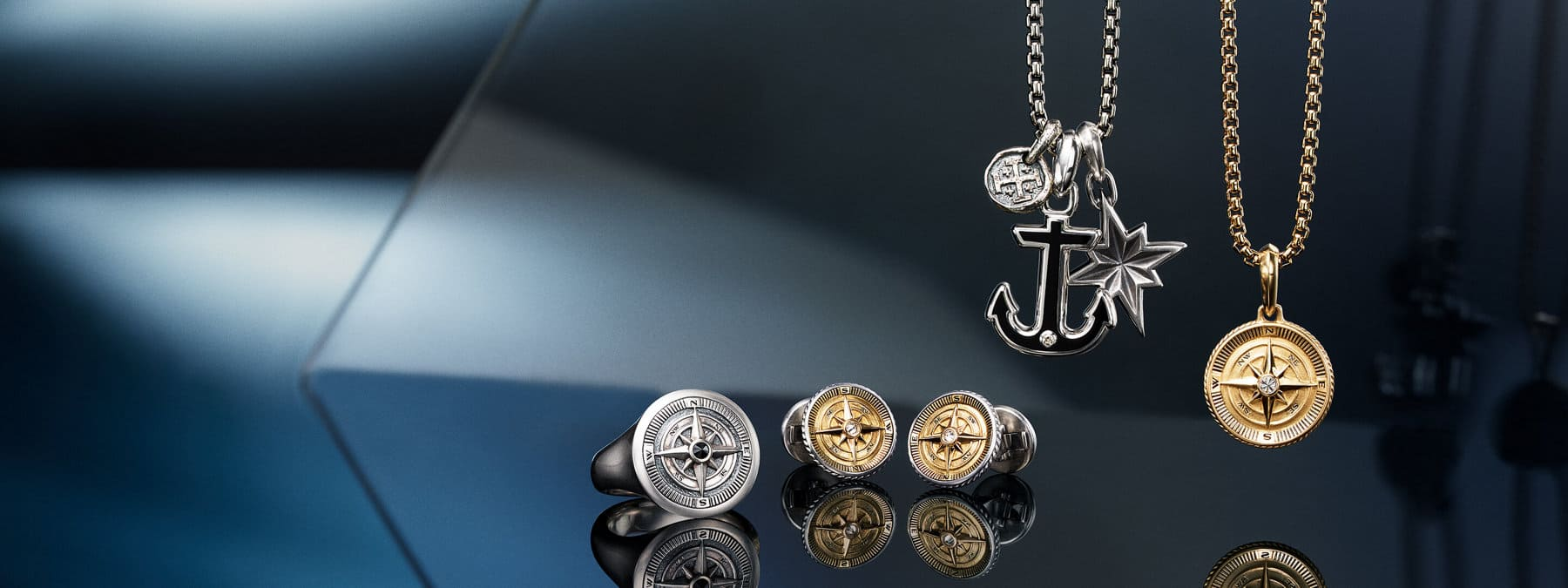 A color photograph shows a horizontal arrangement of David Yurman men's designs from the Maritime®, Shipwreck and Chain collections atop and in front of reflective surfaces with angular, multi-colored reflections of light and jewelry. The Maritime® compass ring is crafted from sterling silver with a black diamond center stone. The pair of Maritime® compass cufflinks is crafted from sterling silver with 18K yellow gold and white diamond center stones. The sterling silver Shipwreck coin amulet is strung on a sterling silver box-chain necklace with two Maritime® amulets: an anchor crafted from sterling silver with black onyx, and a north star crafted from sterling silver. The final Maritime® compass amulet is crafted from 18K yellow gold with a diamond center stone, and is strung on an 18K yellow gold box-chain necklace.