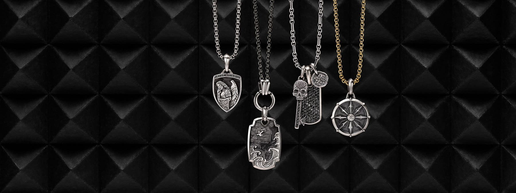 A color photo shows four David Yurman men's box-chain necklaces in sterling silver or darkened stainless steel arranged in a row atop a dark, stone pyramid-patterned surface with stark shadows. Each necklace is strung with one or three David Yurman men's amulets crafted from sterling silver. From left to right are a Saint Michael amulet, a Waves tag with forged carbon, a Petrvs skull pendant with pave black diamonds, a Streamline tag with pavé black diamonds, a Shipwreck coin amulet and a Petrvs sterling silver dharma wheel amulet with a single white diamond.