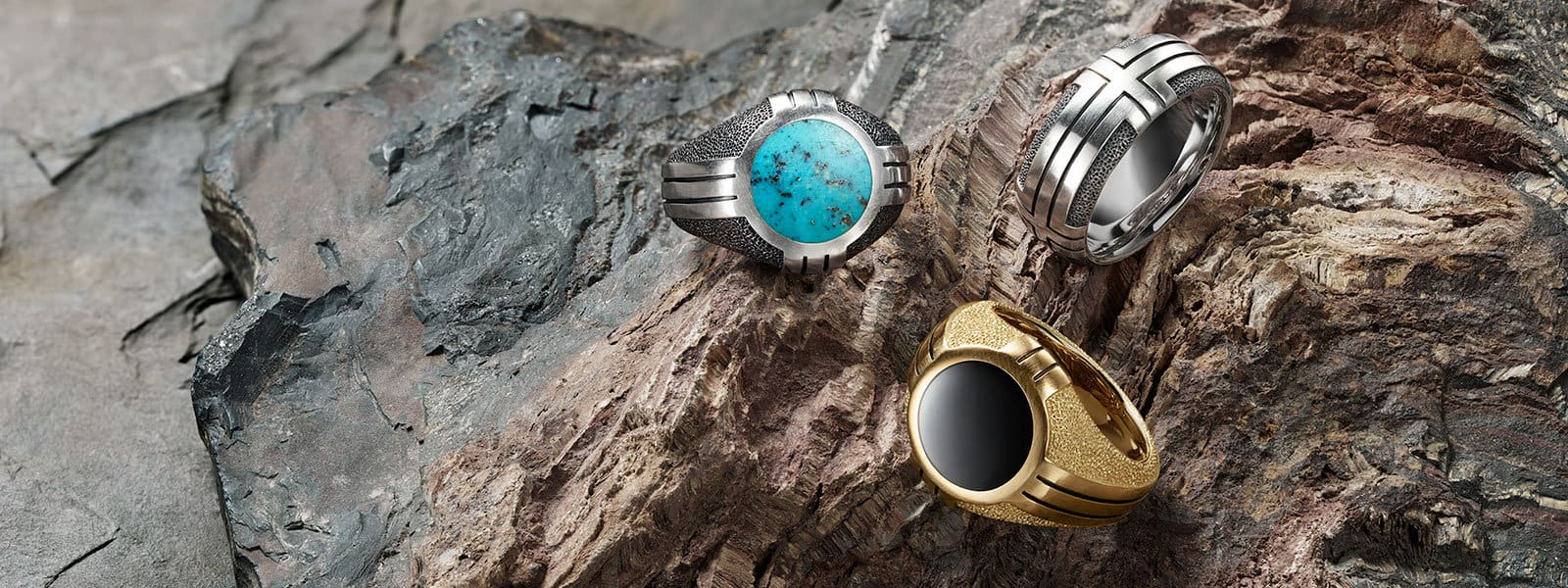 Southwest signet rings in sterling silver with turquoise, 18K yellow gold with black onyx and a Southwest band in sterling silver arranged on the ridges of a multicolored stone.