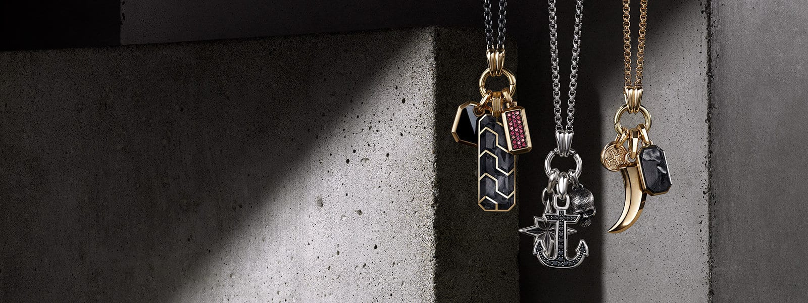 David Yurman Men's Roman, Forged Carbon and Streamline pendants in 18K gold with or without black onyx, forged carbon or rubies; Maritime or Petrvs pendants in sterling silver with or without black diamonds; or Shipwreck, Roman and Forged Carbon pendants in 18K gold with or without forged carbon, arranged in three groups, each hanging on an Amulet Necklace in mixed metals, sterling silver, or 18K gold, in front of textured stones illuminated by rays of light.