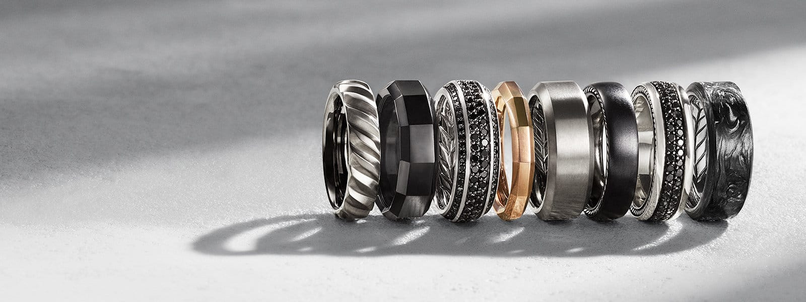 A row of David Yurman Men's The Cable Collection, Faceted, Beveled and Streamline men's bands in a mix of grey or black titanium, sterling silver, or 18K rose gold with or without black diamonds or forged carbon, on a textured white stone with long shadows.