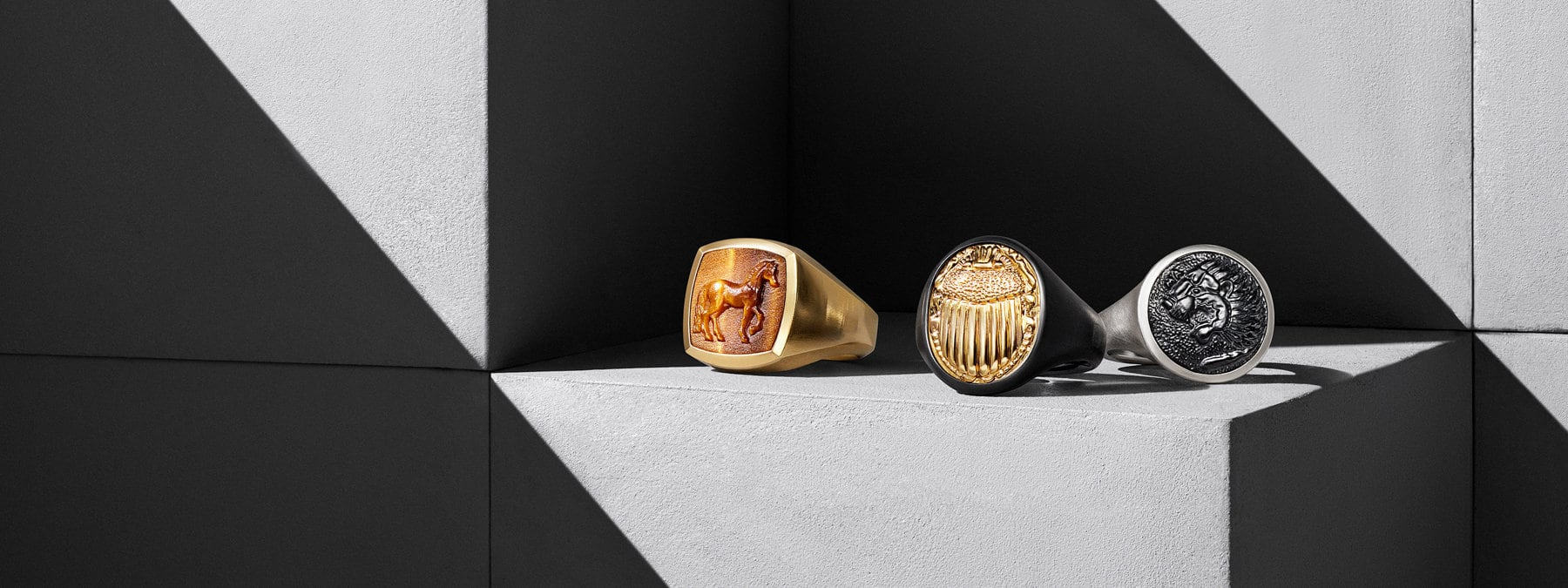 A color photograph shows three David Yurman men's signet rings from the Petrvs collection in a row atop grey concrete cubes with graphic shadows. One ring features a horse motif and is crafted from 18K yellow gold with tiger's eye. One ring features a scarab motif and is crafted from black titanium with 18K yellow gold. The final pinky ring features a lion motif and is crafted from sterling silver.