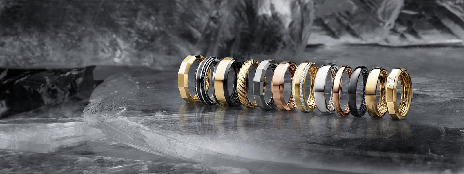 A row of men's bands in a mix of 18K yellow of rose gold, sterling silver, black or grey titanium with or without white or black diamonds, on a sheet of ice.