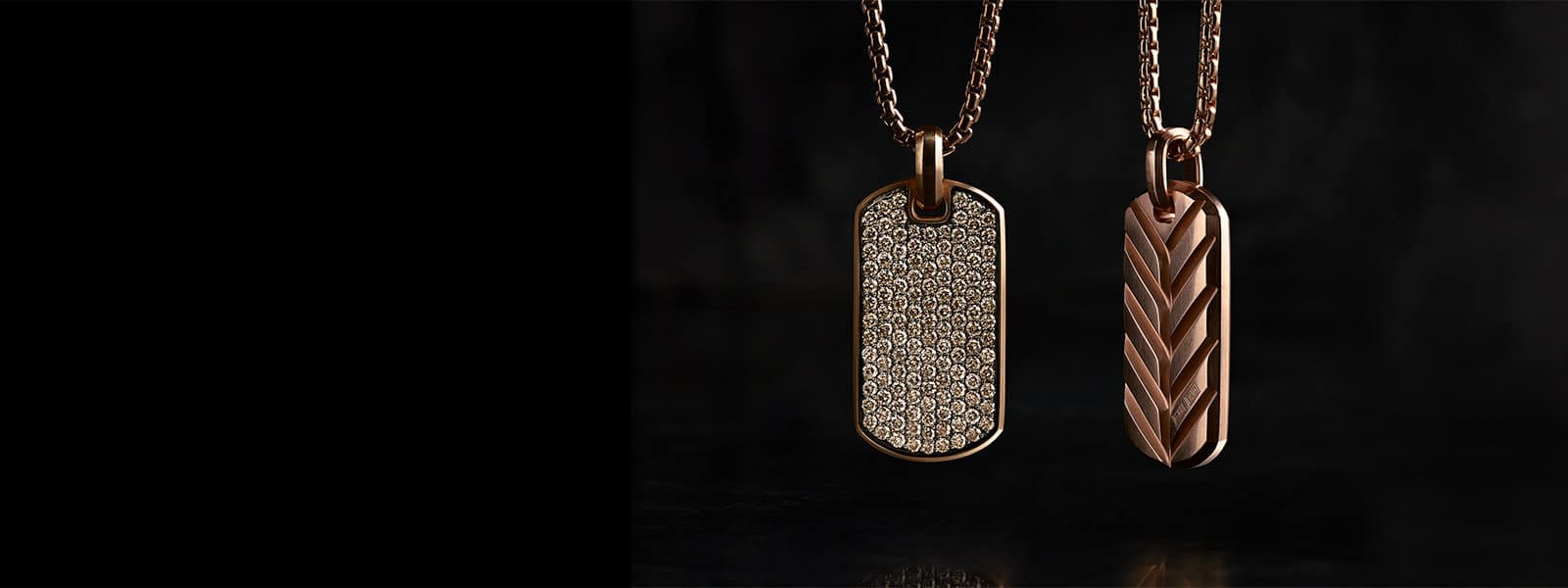 A David Yurman men's Streamline® tag in 18K rose gold with cognac diamonds, hanging on an 18K rose gold chain above a dark, reflective surface.