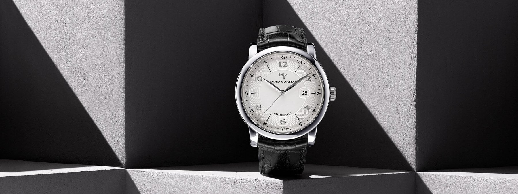 A color photograph shows a David Yurman men's Classic timepiece standing upright on its straps in front and on top of a gray stone surface with graphic shadows. The watch is crafted with a stainless-steel case, automatic movement and a matte alligator strap.