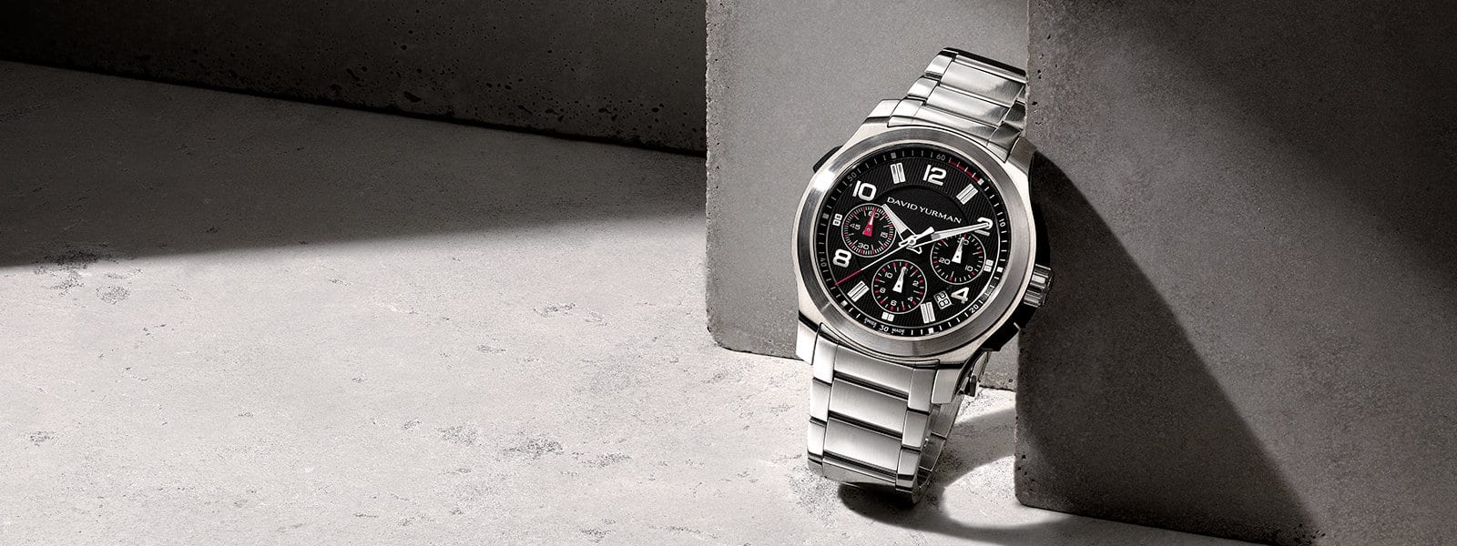 A David Yurman Men's Revolution 43.5mm chronograph watch in stainless steel leaning upright against a grey textured stone and casting a long shadow.