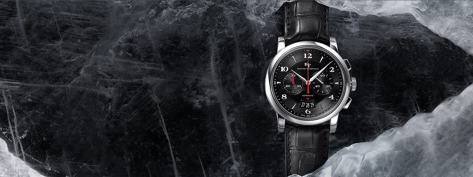 A Classic 43.5mm watch in stainless steel with a black embossed leather strap and black watch face, wrapped around a sheet of dark, scratched ice.