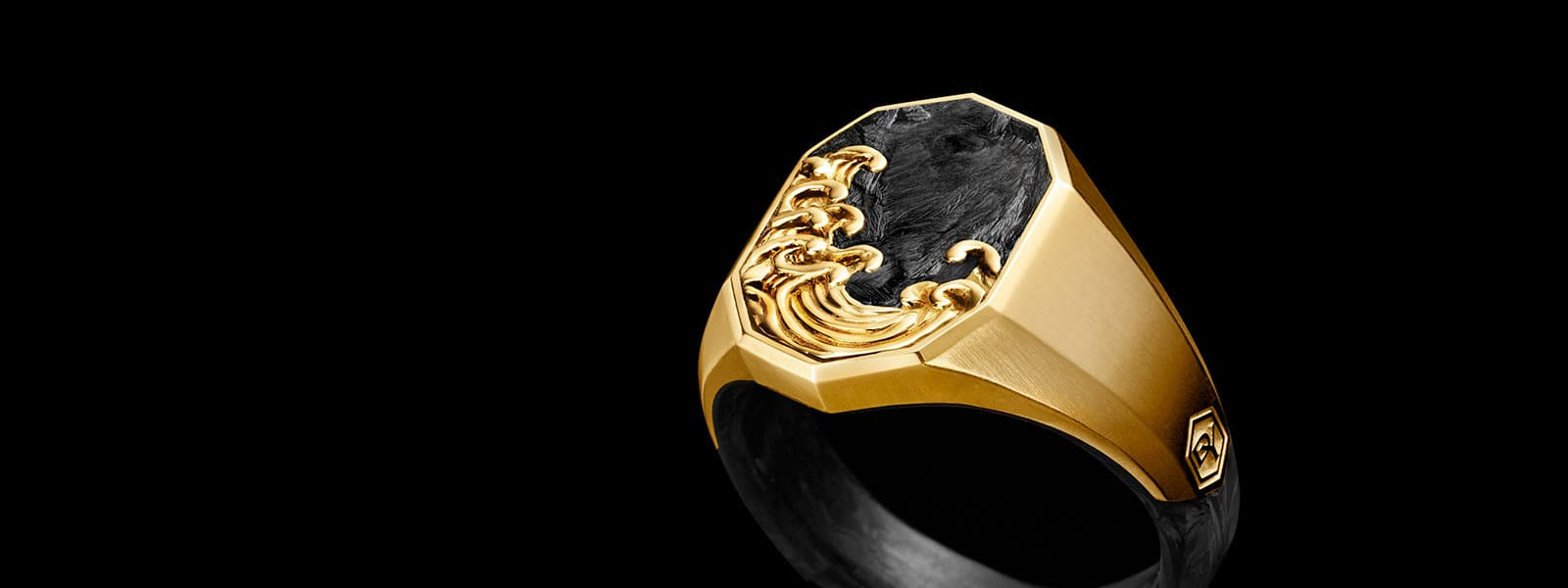 A David Yurman men's Waves signet ring in 18K yellow gold with forged carbon on a dark reflective surface.