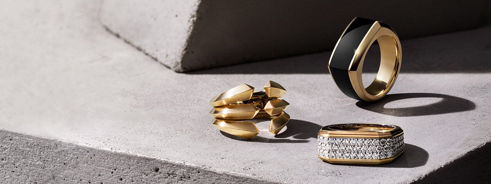 Three David Yurman men's Roman and Pavé rings, in 18K yellow gold with or without black onyx or white diamonds, in a group on a light grey stone and casting long shadows.
