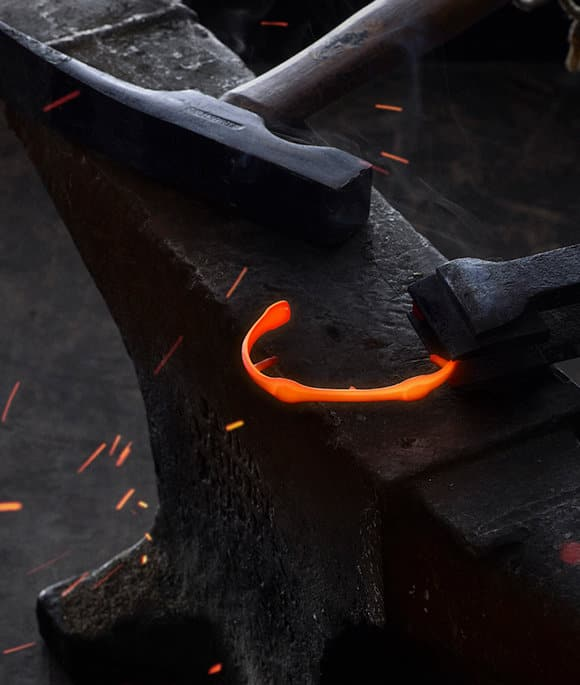 An Anvil cuff bracelet glows orange with intense heat as it is held on an anvil next to a hammer.