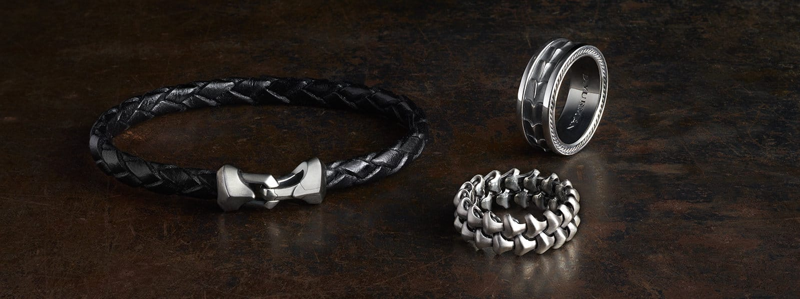 Armory® black leather bracelet and band rings in sterling silver on a dark-reddish, scratched stone.