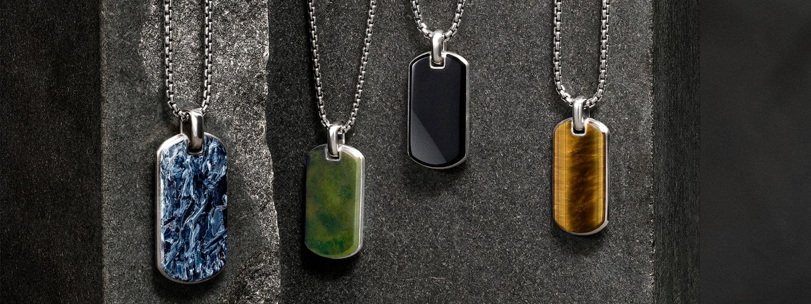 Exotic Stone tags in pietersite, jade, black onyx and tiger's eye, laying against flecked stones.