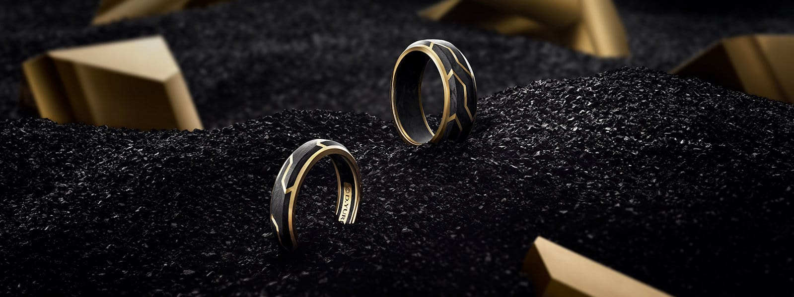 Forged Carbon band rings in 18K yellow gold stick out from a pile of forged shavings and gold blocks.
