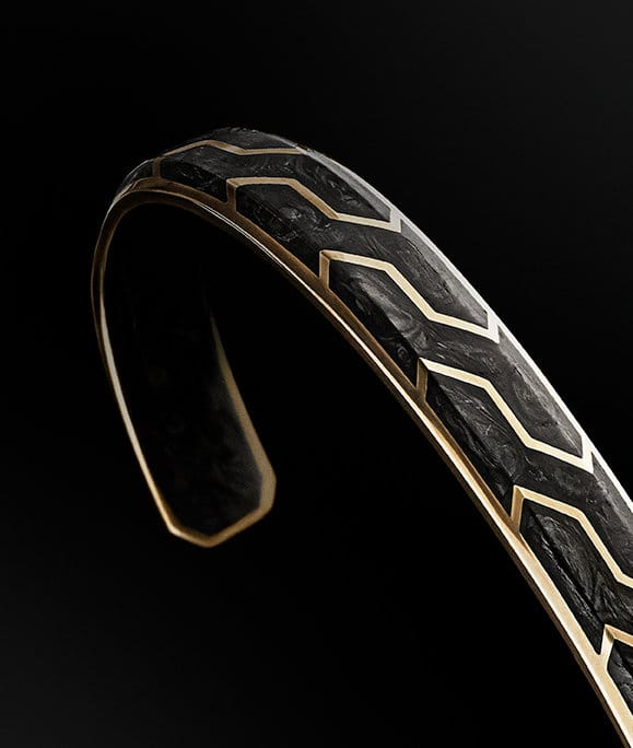 A Forged Carbon cuff bracelet in 18K yellow gold.