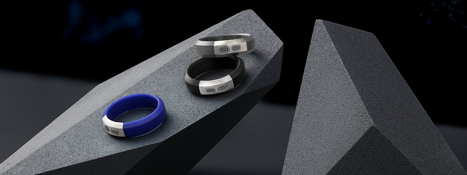 Hex band rings in blue, black and grey rubber with sterling silver on a faceted stone.