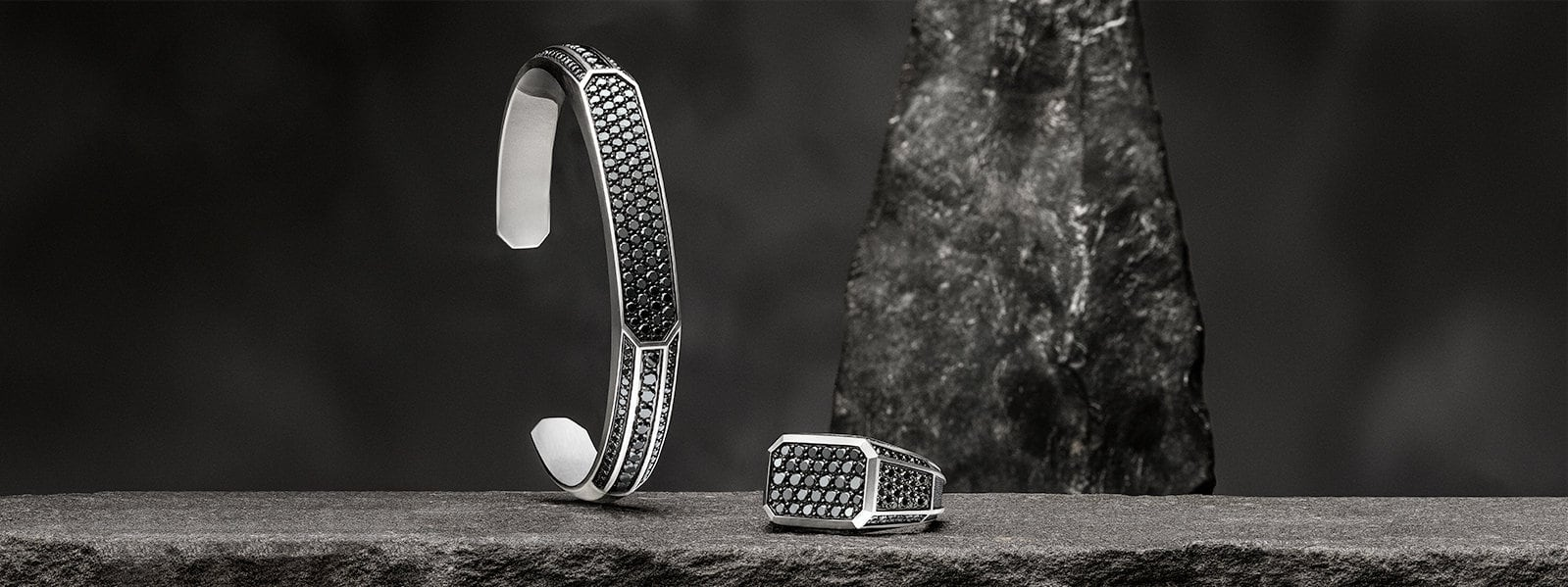 A Pavé cuff bracelet and signet ring in sterling silver with black diamonds on a textured stone.