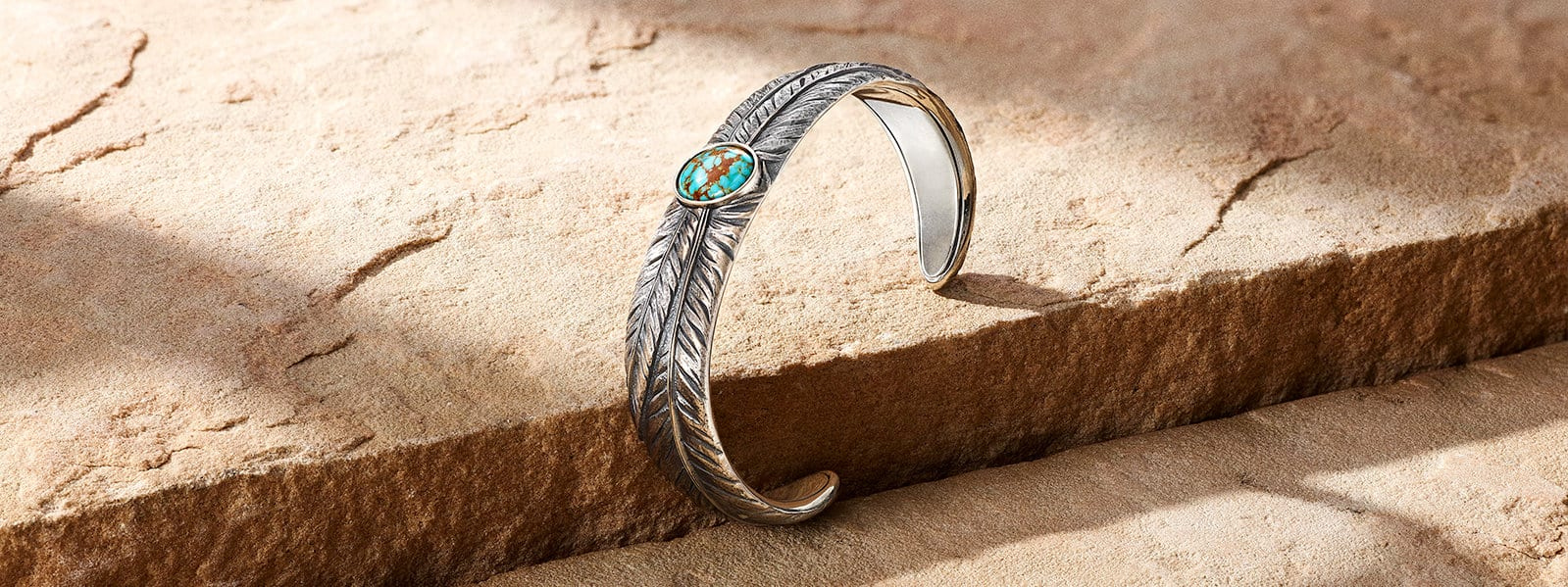 Southwest feather cuff bracelet in sterling silver with turquoise on warm-hued stone.
