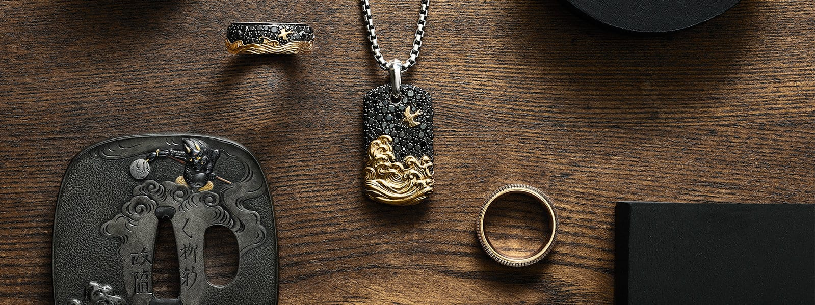 Waves band rings and a tag, along with an 18th century samurai sword tsuba, on a wood surface.