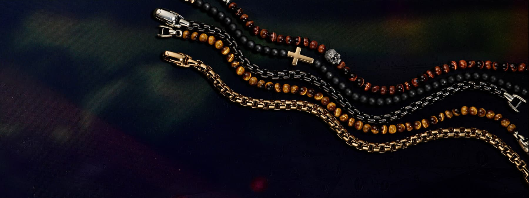 A color photograph shows a row of five David Yurman men's bracelets from the Spiritual Beads and Chain collections atop a colorful backdrop illuminated by light. Two bracelets are crafted from 18K yellow gold or black titanium with sterling silver. Three of the bracelets are crafted from sterling silver with beads of black onyx or tiger's eye.