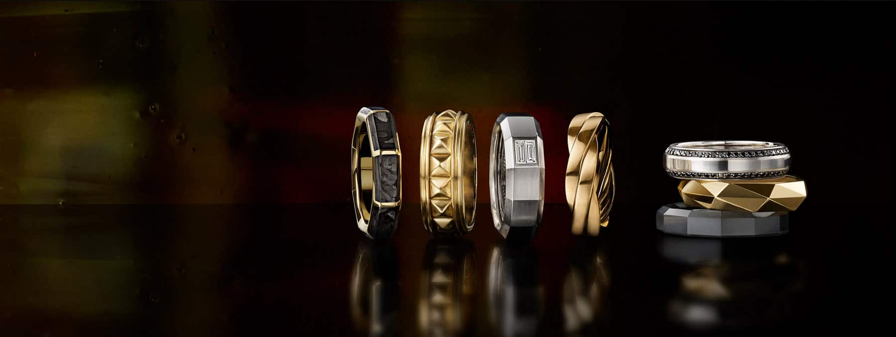 A color photograph shows a horizontal row of four David Yurman men's band rings next to a vertical stack of three David Yurman men's band rings in front of a colorful stained glass panel illuminated by light. The rings are crafted from black titanium, 18K yellow gold with or without forged carbon, 18K white gold with a baguette-cut white diamond or pavé black diamonds.