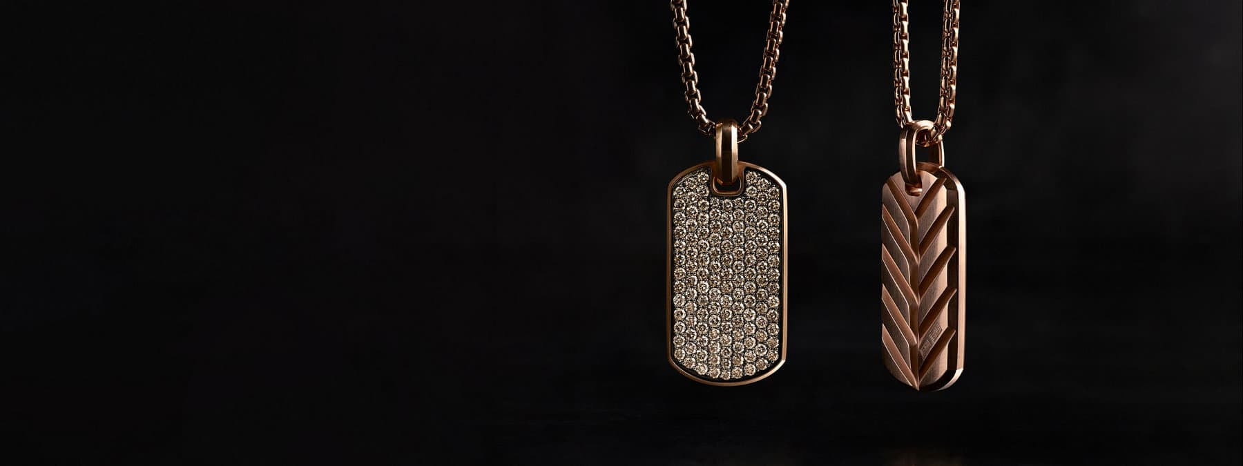 A color photograph shows two David Yurman men's tags strung on box-chain necklaces. The jewelry is crafted from 18K rose gold with pavé diamonds. One tag shows Chevron detailing while the other tag is covered with diamonds