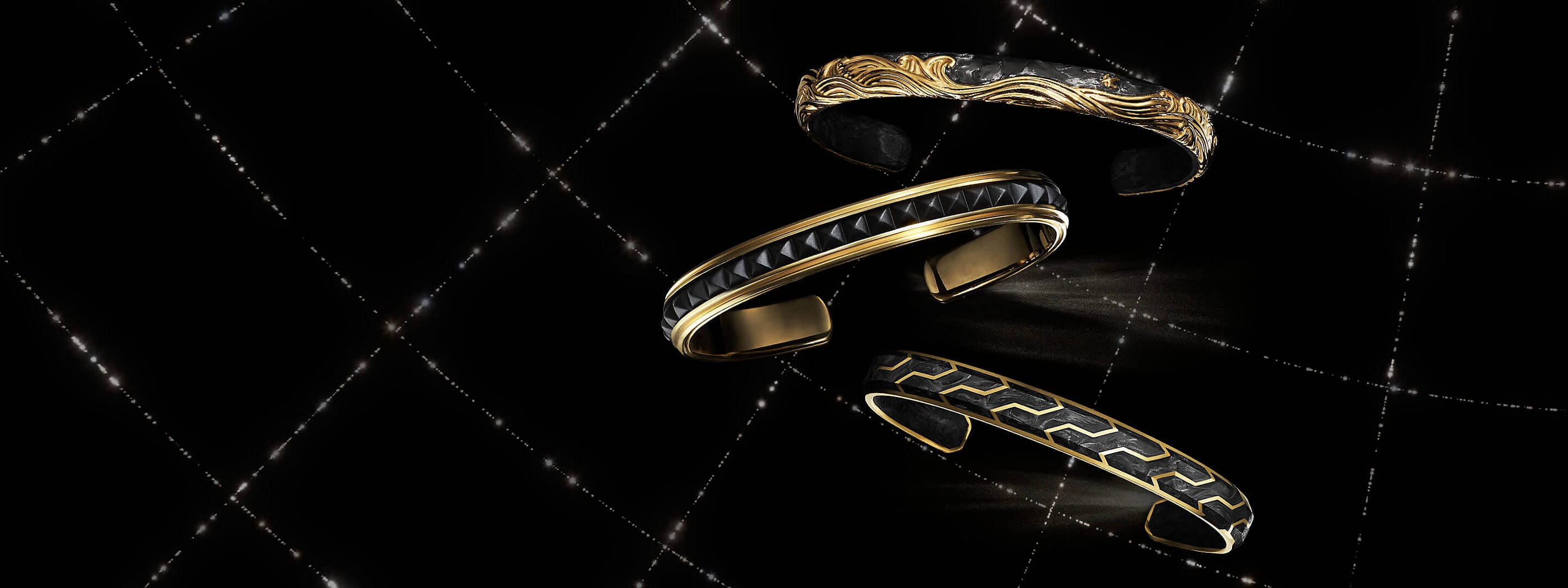 A color photo shows three David Yurman men's bracelets floating in front of a black background with white latitude and longitude lines. The jewelry is crafted from 18K yellow gold with or without forged carbon or black titanium.