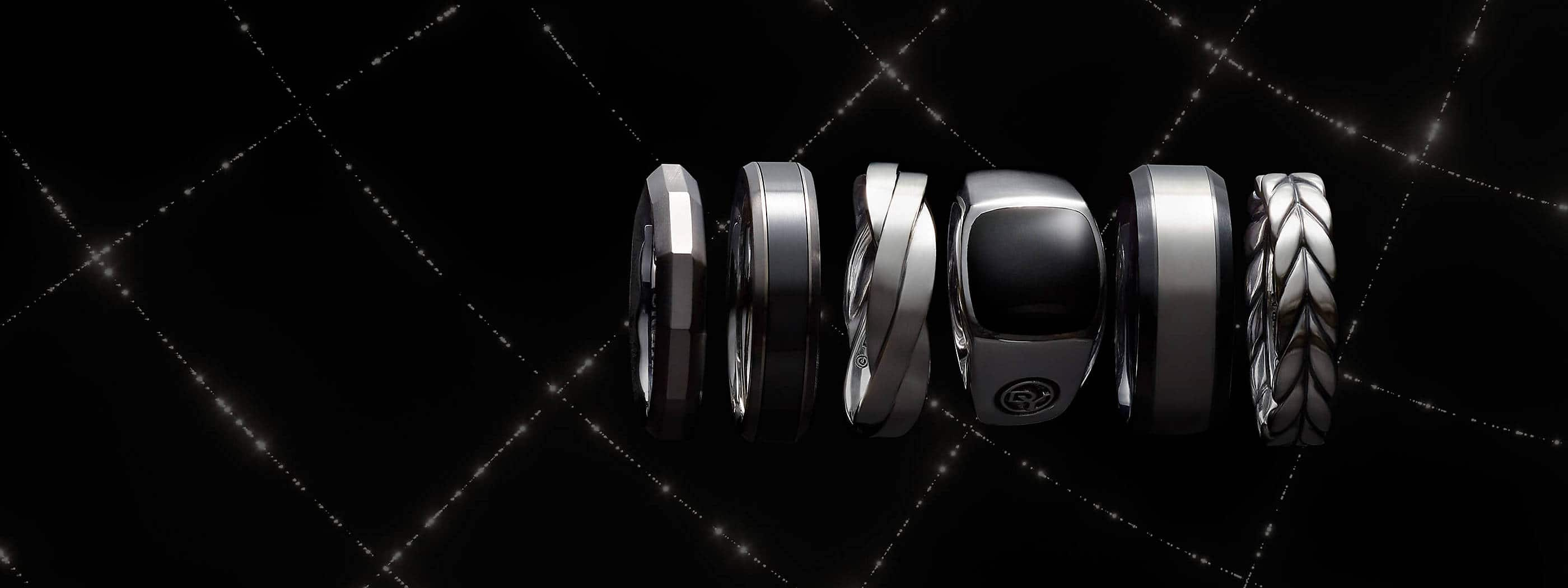 A color photograph shows a horizontal row of seven David Yurman men's bands from the Faceted, Beveled, Cable, Streamline and Chevron collections floating in front of a black background with white latitude and longitude lines. The jewelry is crafted with grey or black titanium with sterling silver, or sterling silver.