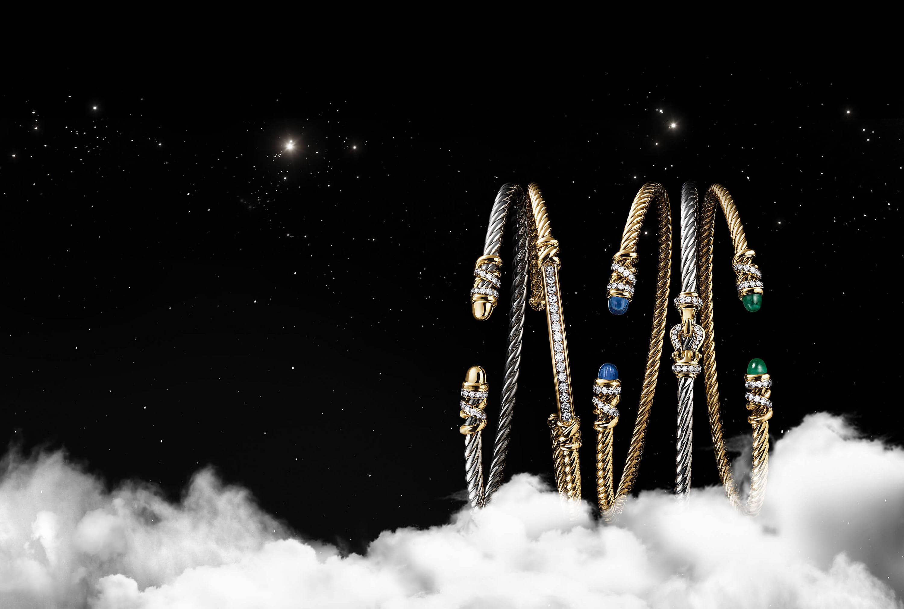 A color photo shows an overhead shot of a horizontal stack of five David Yurman bracelets from the Helena and Buckle collections floating in a starry night sky with white clouds. Three of the women's bracelets are crafted from 18K yellow gold with pavé diamond, emerald or tanzanite accents. Two of the women's bracelets are crafted from sterling silver with 18K yellow gold and pavé diamond accents.
