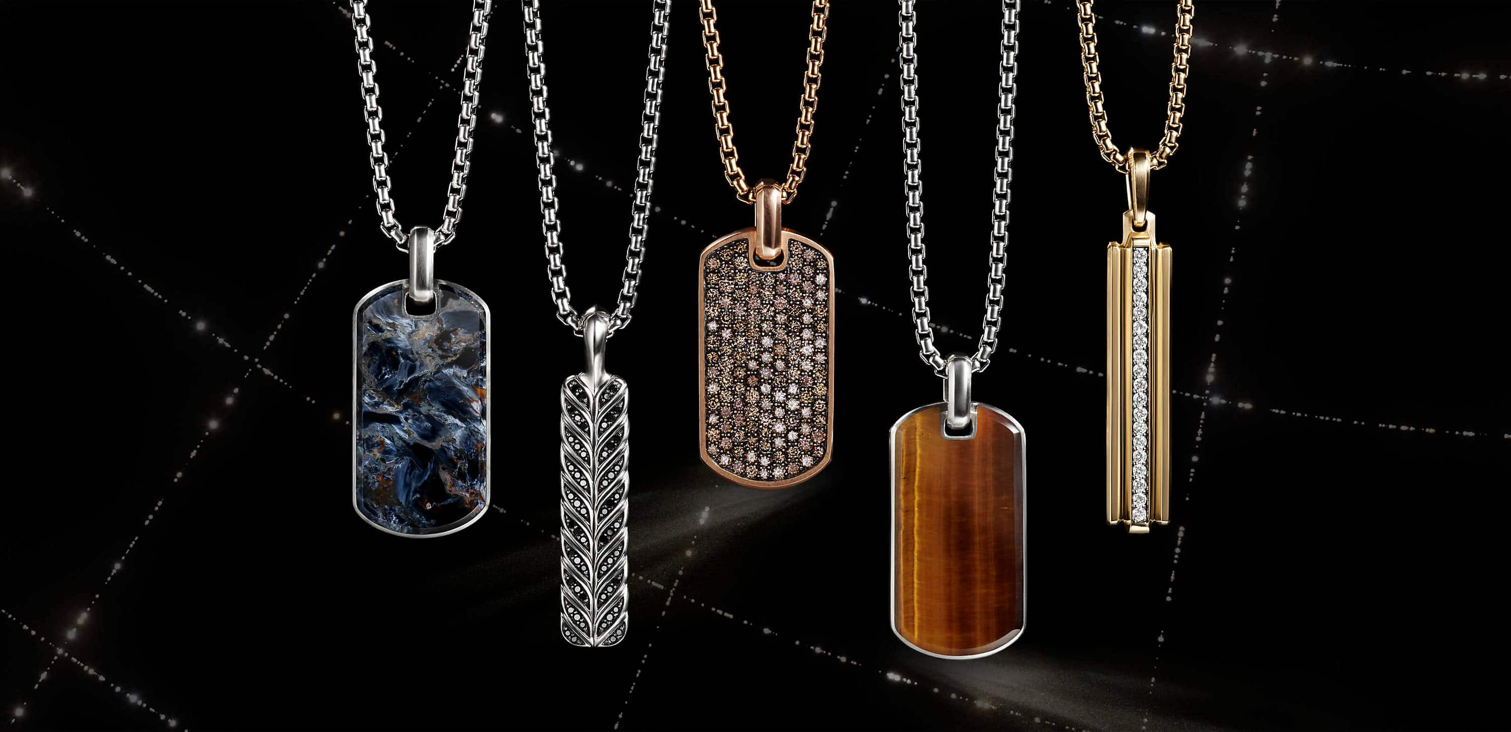 A  color photograph shows five David Yurman men's tags strung on box chains hanging in front of a black background with white latitude and longitude lines. Three of the tags are crafted from sterling silver with pietersite, black diamonds or tiger's eye. One tag is crafted from 18K rose gold with cognac diamonds. The final tag is crafted from 18K yellow gold with white diamonds.