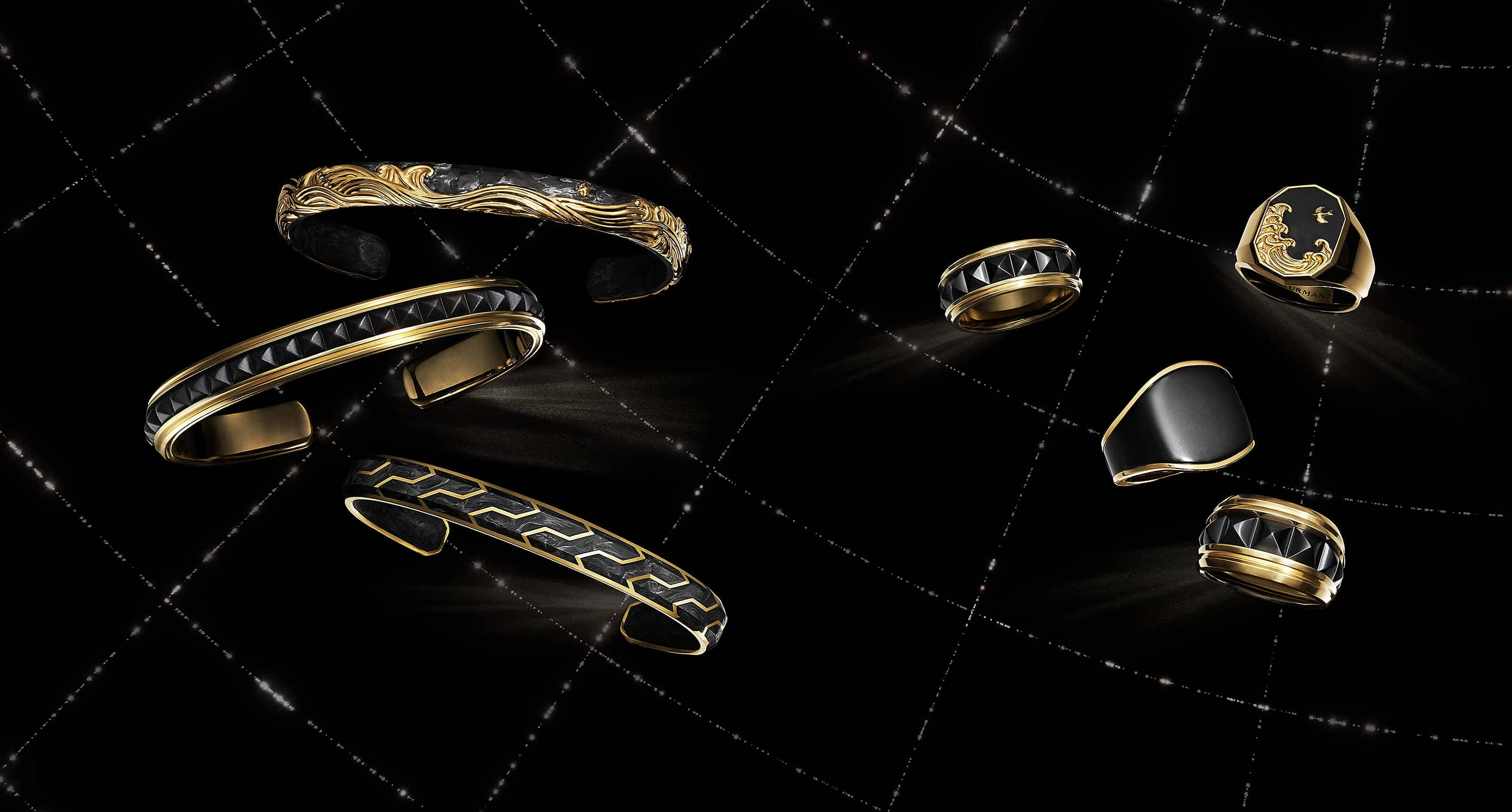 A color photo shows three David Yurman men's bracelets and four men's rings floating in a night sky with white latitude and longitude lines. The jewelry is crafted from 18K yellow gold with or without forged carbon or black titanium.