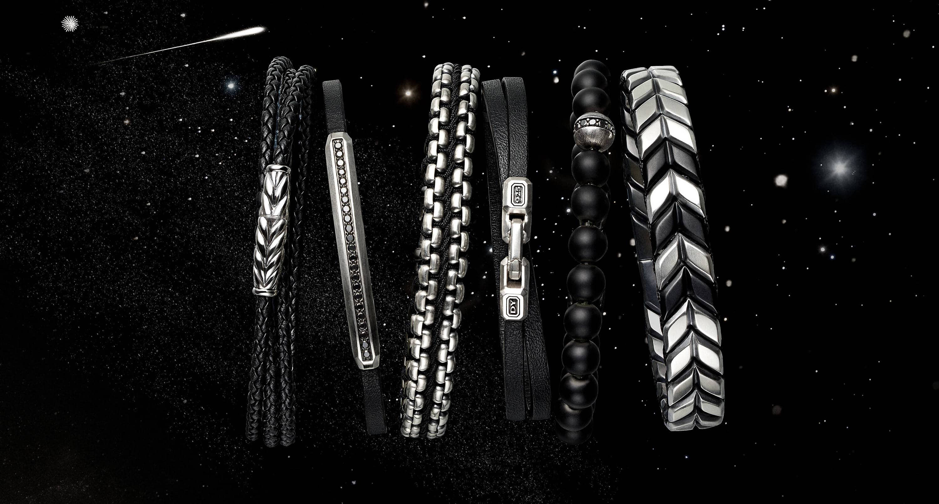 A color photo shows a horizontal stack of six David Yurman men's bracelets from the Streamline, Chain and Chevron collections floating in front of a starry night sky. The jewelry is crafted from sterling silver with or without black leather, diamonds, woven nylon, onyx or titanium.