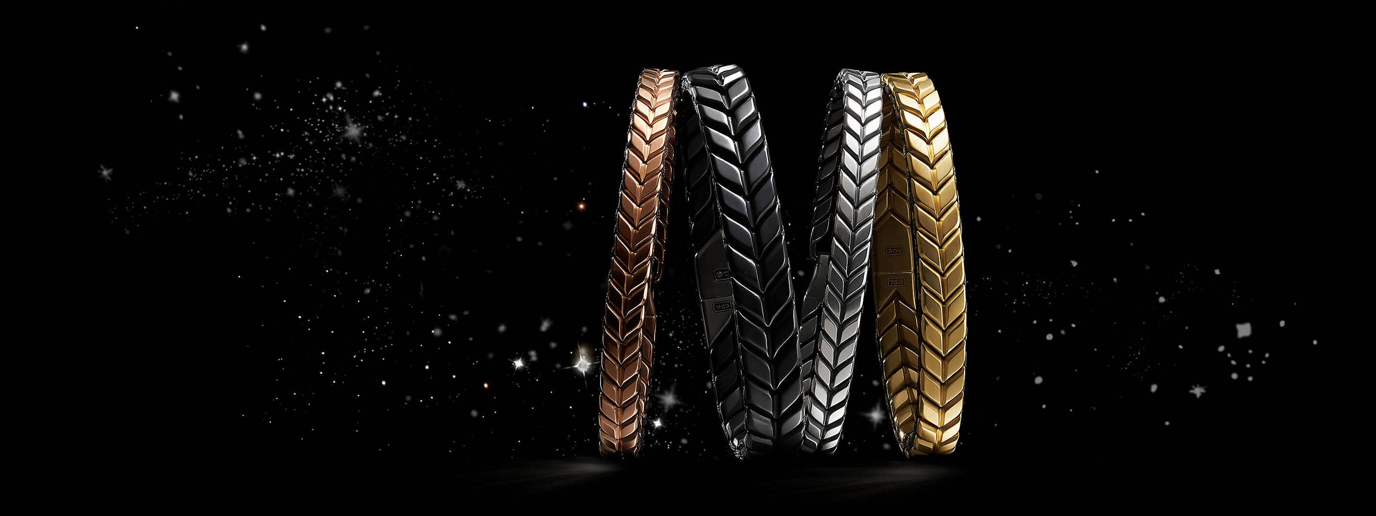 A color photograph shows a horizontal stack of four David Yurman men's Chevron bracelets leaning against each other in front of a starry night sky. The bracelets are crafted from 18K rose gold, black titanium with sterling silver, sterling silver or 18K yellow gold.